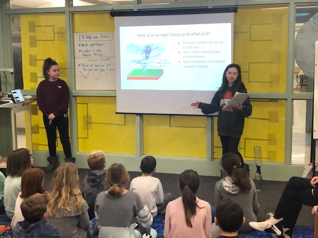 two students presenting to younger students