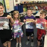 students holding donated helping hands bags.